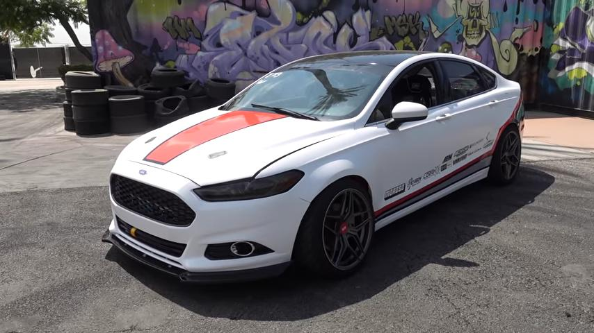 What you see here may seem like a mundane 2016 Ford Fusion Sport, but don't be mistaken: the car packs a second-gen 5.0 Mustang Coyote V8 with 450 hp (336 kW) and is a true drift monster!